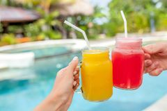 Two colorful fruit shakes in hands. Summer and tropical mood. Cold blended drinks, mango and watermelon fruit smoothie royalty free stock photos