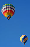 Two Colorful Hot Air Balloons. Two hot air balloons soar in a beautiful blue sky Stock Photos