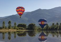Two Colorful Hot-air Balloons. 2 colorful hot-air balloons above a lake in Rocky Mountains. Colorado state flag balloon reflection in lake royalty free stock photography
