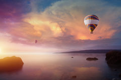 Two colorful hot air balloons flies in glowing sunset sky. Amazing heavenly background - two colorful hot air balloons flies in glowing sunset sky above calm sea royalty free stock image