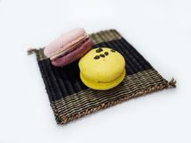 Two colorful macaroons lay on the wooden mat stock photography