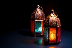 Two colorful oriental Lamp lanterns burn with candles with color. Reflection on dark black background for Ramadan and other islamic muslim holidays, space for Stock Photo