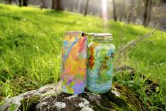 The Feminine Art Project. Two colorful painted glass jars and paint brushes on top of a mossy rock in a field of grass, sun ray shining into one of the jars Stock Images
