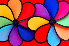 Two colorful pinwheels. A variety of colors of cambridge blue,navy blue,pink,crimson,purple, red, orange and black. Nice beautiful curves, revolving Stock Images