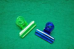 Two colorful plastic bulldog clips. On a green background royalty free stock photo