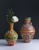 Two colorful pottery vases with yellow flower on black background Royalty Free Stock Images