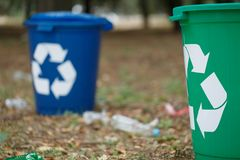 Two colorful recycling bins on a blurred natural background. Containers for garbage recycling. Ecology, recycling. A close-up of a couple of bright blue and Stock Photography