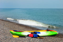 Two colorful sea kayaks with paddles and life jackets on stony b Stock Photography