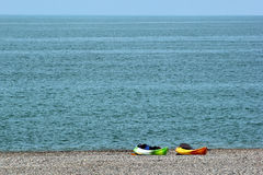 Two colorful sea kayaks with paddles and life jackets on stony beach Royalty Free Stock Photo