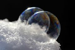 Two colorful soap bubbles on snow.  Stock Photo