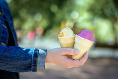 Two colorful tasty ice cream cones in hand. Royalty Free Stock Image