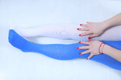 Two colors stockings. Girl wearing two colors leggings, white and blue, red nails Stock Photos