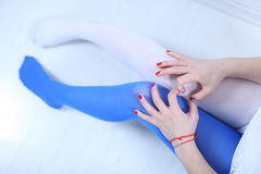 Two colors stockings. Girl wearing two colors leggings, white and blue, red nails Royalty Free Stock Photo