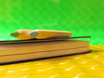 Two colour pencils and a notebook on green and yellow glossy background. Wooden coloured pencils on the top of closed black notebook. 3D glossy paper background Stock Image