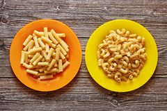 Two colour plates with pasta on a wood background royalty free stock images