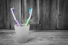 Two coloured tooth brushes in a plastic cup. Stock Photo