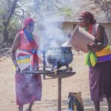 Two African tribal women cooking in cauldron stock photography