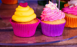 Two colourful cupcakes on street market. Royalty Free Stock Image