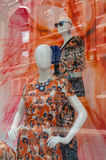 Two Colourful Mannequins in a Shop Window. Two colourful mannequins with bright colourful dresses in a shop window. A street scene reflecting in glass Royalty Free Stock Photo