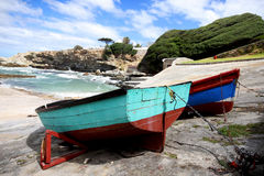 Two colourfull fishing boats docked. Close up photo of sea fishing boats docked with the ocean in the background Stock Image