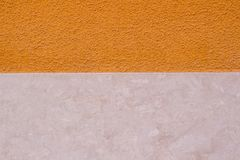 Two colours wall background. Orange painted and beige marble wall.  Stock Image