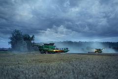 Two combines on a field in the evening. Landscape shot of a half cut wheat field with dramatic cloud formations. Two combine harvester at work Royalty Free Stock Image