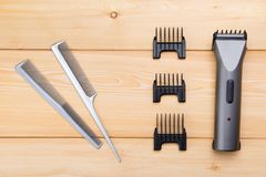 Two combs with attachments for electric cars, for hair cutting, on wooden boards stock photos