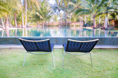 Two  comfortable lounge chairs on the green grass near the swimmi Stock Image