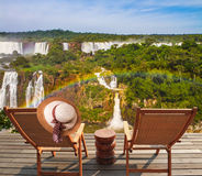 Two comfortable wooden chaise lounges. Face waterfalls. On one hangs an elegant straw female hat Concept of active and eco-tourism. Incredible exotic waterfalls stock photography
