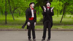 Two comical mimes do performance in the park. Two mimes in black hat, suit, white shirt and red bow do performance in park. Funny actors whisper to each other stock video
