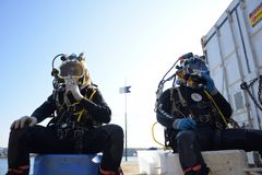 Two commercial divers before the dive. Two commercial divers pre dive check ready for the dive royalty free stock photography