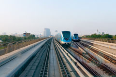Two commuter trains pass each other on elevated, parallel tracks. DUBAI, UAE - 16 JULY 2014: Two commuter trains pass each other on elevated, parallel tracks in Royalty Free Stock Image