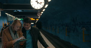 Two commuters using tablet PC at metro station. Young man and woman using touch pad in the underground. They standing on the platform under big clock, train stock footage