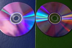 Two compact discs on a blue green surface stock photography