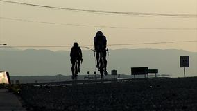 Two competing cyclists approach the camera at the dawn. Cycling contestants advancing on racing track through America stock footage
