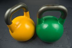 Two competition kettlebells inside a gym. Yellow and green competition kettlebells on a fitness studio gym floor. Yellow competition kettlebells weigh 16kg royalty free stock photos
