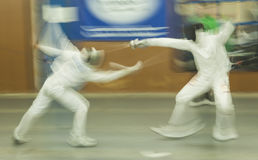 Two competitors fight using swords doing fencing, Madrid, Spai. In this assault of fencing, the two shooters move fast to avoid a touche, semifinals of a Royalty Free Stock Photos
