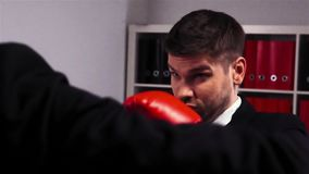Two competitors in gloves boxing in office room stock footage