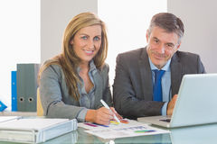 Two concentrated business people smiling at camera trying to understand figures Royalty Free Stock Images