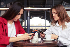 Two concentrated businesswomen working in smartphones Stock Photos
