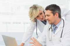Two concentrated doctors using laptop together Royalty Free Stock Images