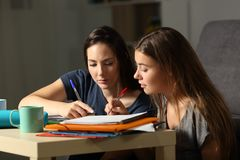 Two students studying together at home late hours. Two concentrated students studying together commenting notes at home late hours Royalty Free Stock Photography