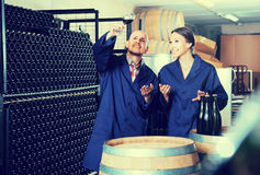 Two concentrated winery workers in aging section of factory. Two concentrated winery workers holding glass of wine in aging section of factory Royalty Free Stock Photos