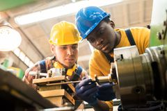 Lathe Operators Working Together. Two concentrated workers wearing protective helmets and rubber gloves using lathe in order to machine workpiece, interior of royalty free stock photo