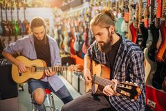Two concentrated young man playing on acoustic guitars. They sit on stools in room full on electric guitars. Bearded stock images