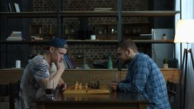 Two clever young men playing chess game at home stock video
