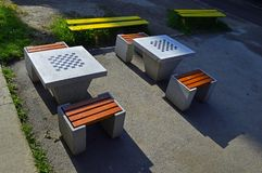 Two concrete chess tables. Four chairs and two yellow lavas stock photos