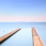Two concrete pier or jetty on a blue sea. Hills on background Stock Images