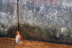 Two concrete slabs of dirty gray color in spots, rusty water flows from the hole. From below, in the foreground there is a liquid rusty from corrosion, a gloomy royalty free stock photography