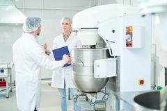 Two confectioners talking standing near machinery at factory royalty free stock photo